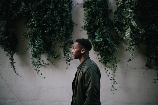 Muž v zelenej bunde stojí pred múrom porasteným brečtanom.jpg