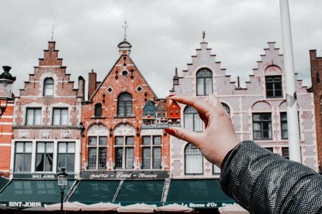 Žena držiaca magnetku budov pred reálnymi budovami