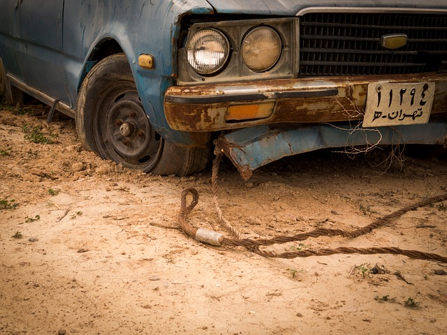 Staré auto, na ktorom je pripnuté ťažné lano