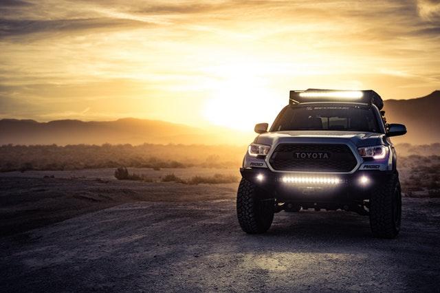 Terénne auto so zapnutými prednými svetlami, zaparkované na piesku a západ slnka