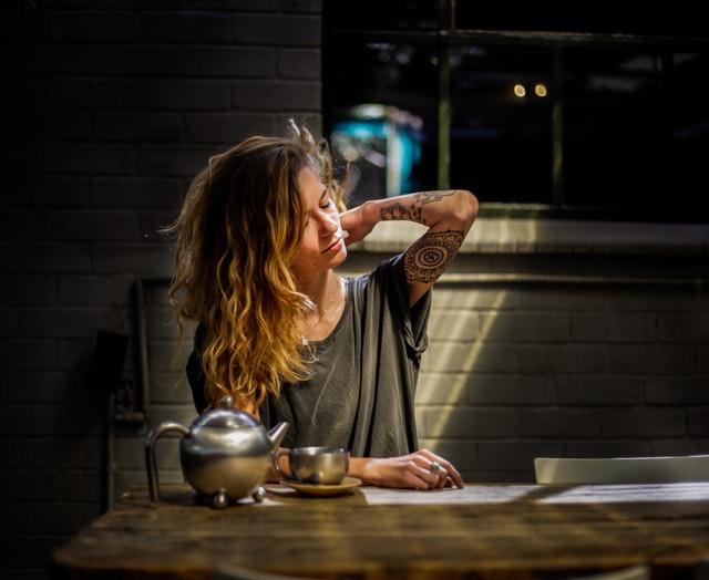 Žena s tetovaním na ruke sedí pri stole, na ktorom je kanvica s čajom.jpg