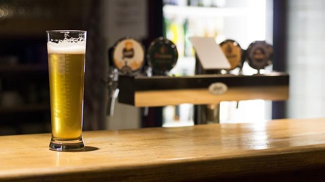 Pivo v sklenenom pohári položené pri výčape.jpg