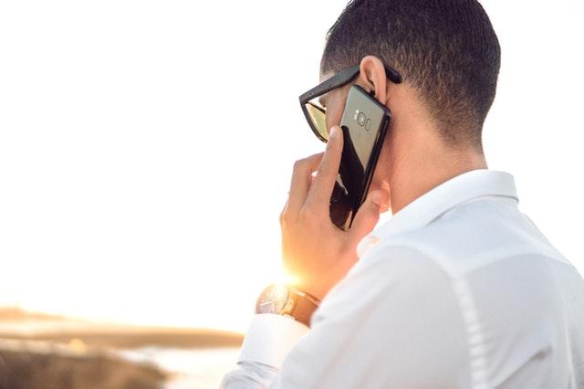 Muž v bielej košeli telefonuje cez mobilný telefón.jpg