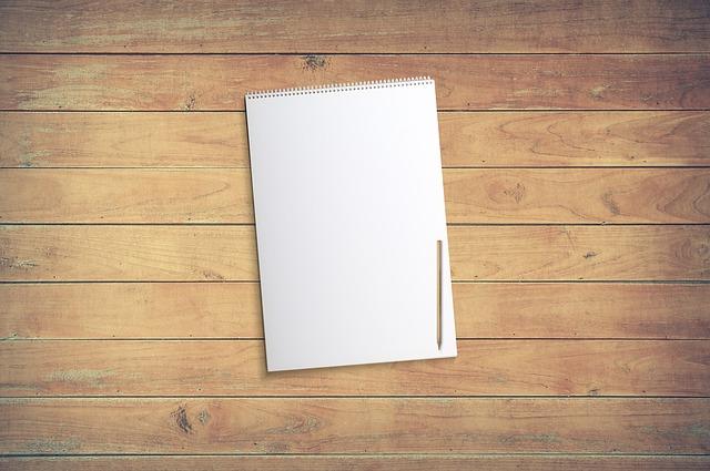 Biely notes položený na hnedom stole.jpg